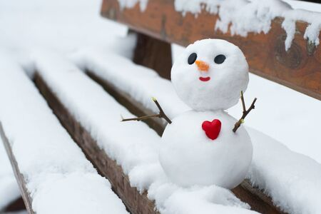 Happy little snowman with a red heart on a snowy bench