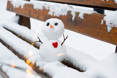 Little snowman with a red heart on a snowy bench Stock Photo