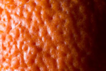 Photo of a bright orange tangerine skin, close-up, macro