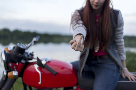 A girl on a red motorcycle shows the middle finger Standard-Bild