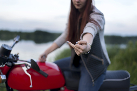 A girl on a red motorcycle shows the middle finger 免版税图像