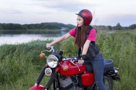 Girl sitting at the wheel of a red vintage motorcycle outdoors Standard-Bild