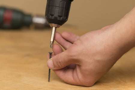 Wireless screwdriver in the hands of a man, on a wooden background, the theme of repair work and building