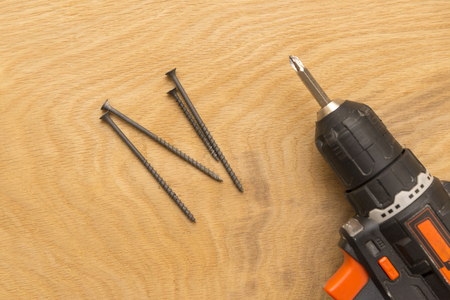 Wireless screwdriver self-tapping screws on a wooden background, the theme of repair work and building, close-up Stock Photo
