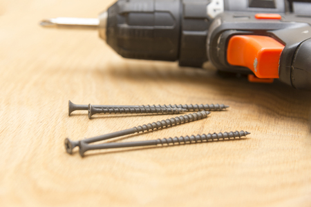 Wireless screwdriver self-tapping screws on a wooden background, the theme of repair work and building, close-up Banque d'images
