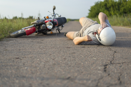The man is lying on the asphalt near his motorcycle, the theme of road accidents 版權商用圖片