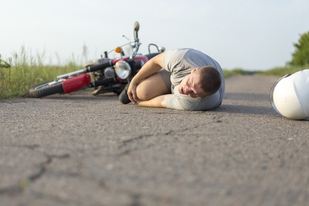 A man holds onto his knee, lying on the asphalt near his motorcycle, the theme of road accidents Stock Photo