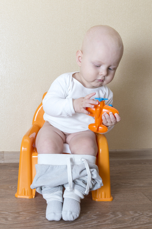 Little baby boy sitting on the pot and playing with toy airplane