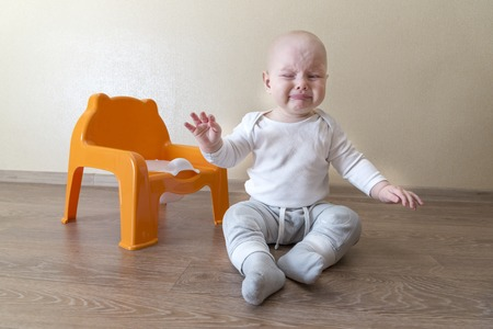 Little baby boy sitting near the pot and crying