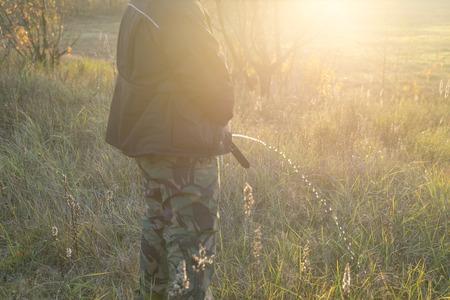 Een man in camouflagebroek plast op de natuur in het gras