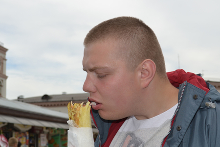 Portrait of a funny guy who eats shawarma with great pleasure Imagens
