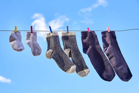 On the clothesline dry the socks of the whole family against the blue clear sky