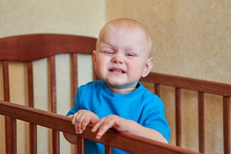 Portrait of a funny boy who grimaces in his crib Standard-Bild - 121820061