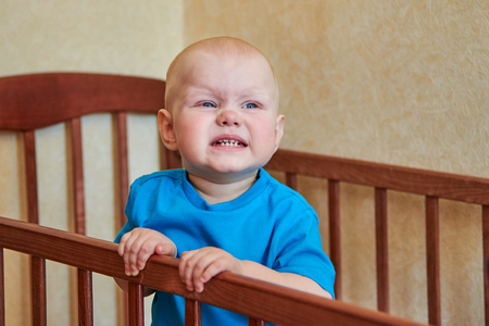 Porträt eines lustigen Jungen, der in seiner Krippe eine Grimasse verzieht