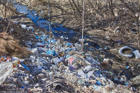 Garbage thrown to the bank of the river, the topic of environmental pollution