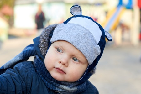 Portrait of a cute little blue-eyed boy with an interested look in a hat, scarf and jacket on the street in early spring