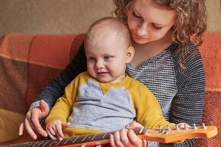 Mom teaches her little cute son to play the guitar. Early child development.