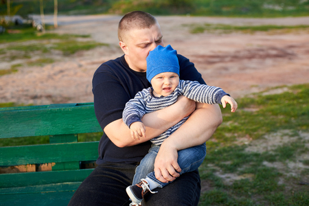 Dad hugs and kisses his little displeased son son on a bench in the park