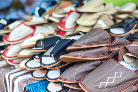 Variety of handmade leather slippers on the market counter