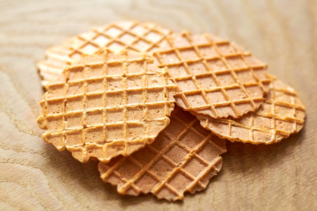 Thin delicious round waffles on a wooden background, close-up Reklamní fotografie