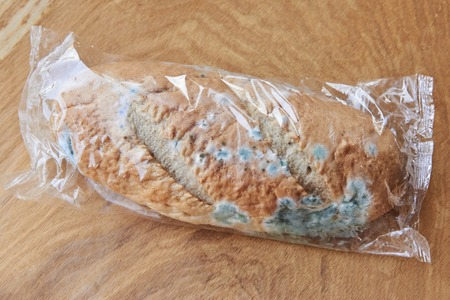 Moldy spoiled bread on a wooden background. Improper storage of food.