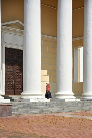 A lonely parishioner walks to the door of an Orthodox church, a beautiful majestic architectural structure.