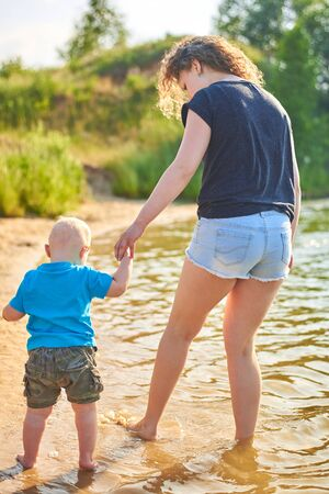 Mom and her little son are walking along the river bank on a hot summer day
