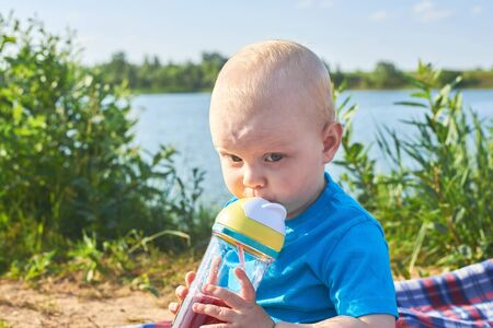 Cute little child drinking from a bottle with a straw on the river bank on a hot summer day