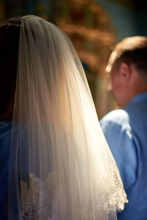Bride in veil and groom at the wedding ceremony in the Christian church. Rear view. Reklamní fotografie