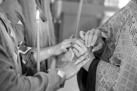 The priest puts the wedding rings on the fingers of the bride and groom at the wedding ceremony in the Christian church. Black and white photo.