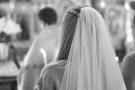 Bride with a candle in the church, the wedding ceremony in the Christian church. Rear view. Black and white photo.