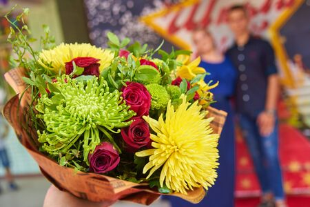 A bouquet of beautiful bright flowers, a couple of young people in the background out of focus Reklamní fotografie