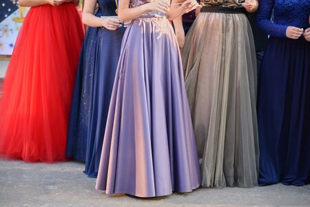 Young girls in long beautiful evening dresses, the lower part