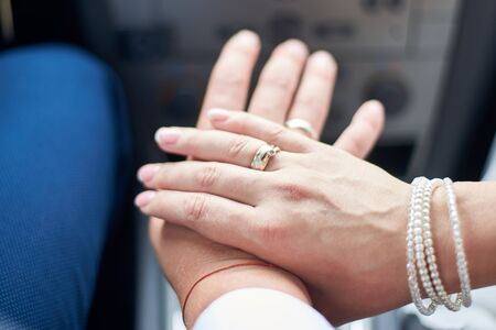Newlyweds in the car show hands with wedding rings on the fingers, close-up.