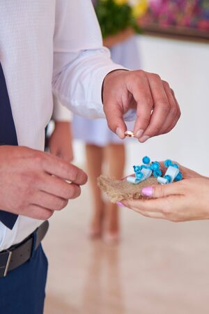 The groom takes the ring to put the bride on the finger at the marriage ceremony on their wedding day