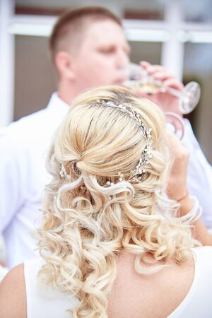 Bride and groom drinking champagne from glasses after the wedding ceremony, back view