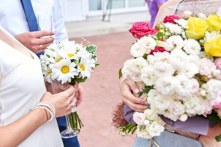 Bride and groom hold glasses of champagne and a bouquet of daisies on their wedding day