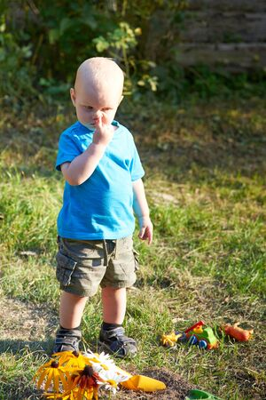 A little boy with a finger in his nose is standing on the grass near his toys on a summer day, the theme of bad children's habits Reklamní fotografie