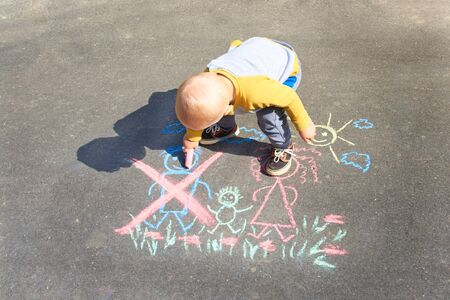 Childrens drawing with colorful chalk on the asphalt, family with no dad. Son crossed out father. Family divorce topic. Фото со стока
