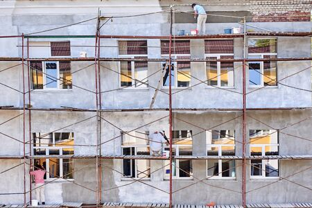Few workers paint and plaster the facade of the house Stok Fotoğraf