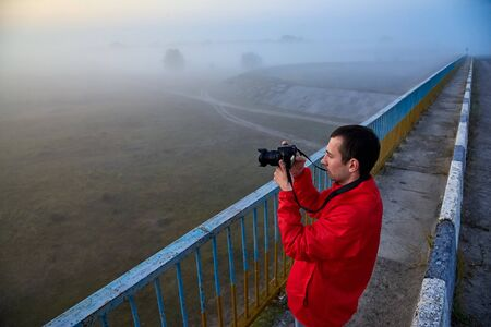 A man on a bridge over the river that photographs a sunrise on a foggy early morning.
