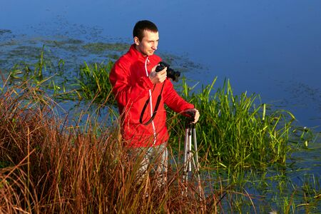 A man stands in a thicket of grass and photographs the river in the early autumn morning. Stock Photo
