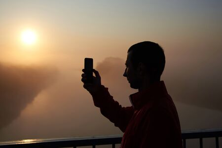 A man on a bridge over the river that photographs on mobile phone a sunrise on a foggy early morning. Stock Photo