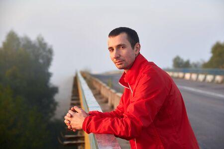 Meditative brunette man on a bridge on a foggy autumn morning.