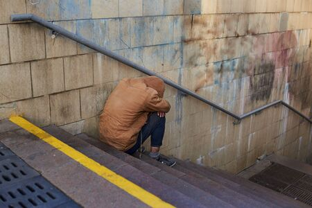 Drunk homeless unhappy man covered his face with his hands and sits on the stairs in the underpass.