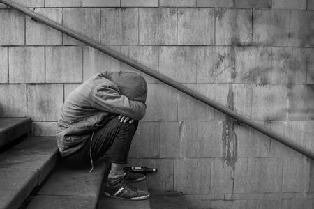 Drunk homeless unhappy man covered his face with his hands and sits on the stairs in the underpass, black and white photo. Stock Photo
