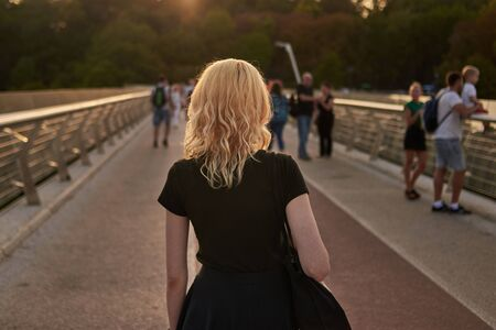 A young blonde woman walks over a city bridge at sunset, back view.