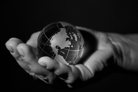 Glass transparent globe, planet Earth, in the hands of a woman, black and white photo. 版權商用圖片