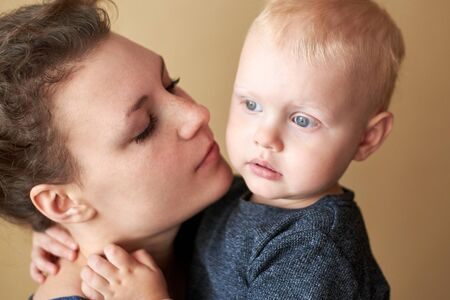 Portrait of a blue-eyed little boy hugging mom by the neck. 写真素材
