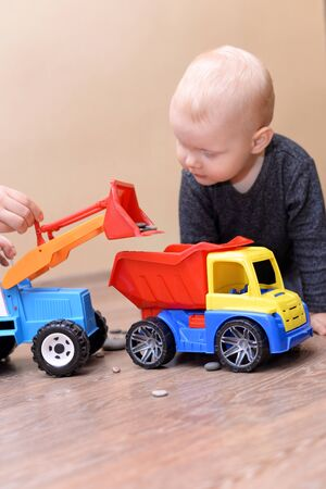 Mom shows her little son how to play with a toy tractor.